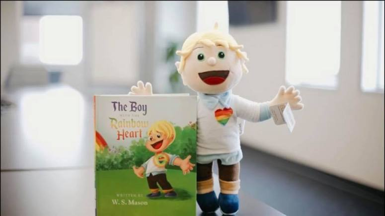 boy with rainbow heart doll